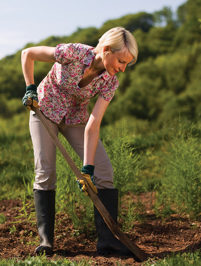 Woman aerating her vegetable garden for spring planting.